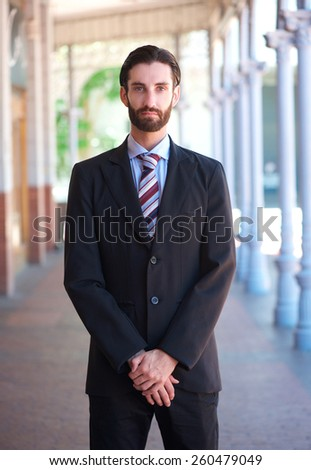 Portrait of a professional businessman standing outdoors in formal suit - stock photo