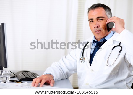 Portrait of a professional friendly senior doctor using a mobile phone - stock photo