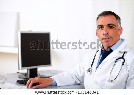 Portrait of a professional mature medicine specialist at hospital workplace - stock photo