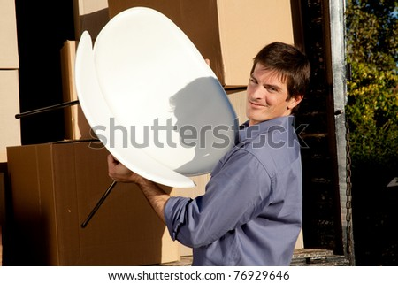 Portrait of a professional mover lifting a chair from a moving truck - stock photo