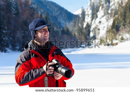 Portrait of a professional nature photographer outdoor in the winter landscape - stock photo