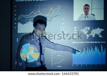 Portrait of a project manager presenting the company'??s activity while his colleague is at the conference by Skype on the foreground  - stock photo