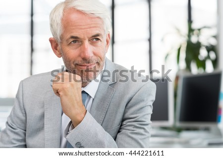 Portrait of a proud businessman in office thinking about a new plan. Portrait of mature businessman with hand on chin looking away. Close up face of a satisfied senior man sitting at a desk in office. - stock photo