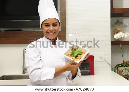 Portrait of a proud chef showing cooking in a modern kitchen - stock photo