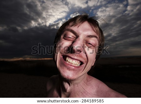 Portrait of a psycho man on a cloudy background - stock photo