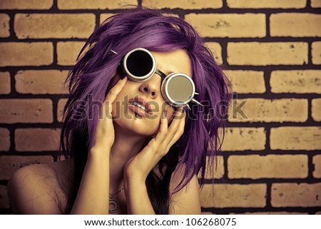 Portrait of a punk girl posing over brick wall.