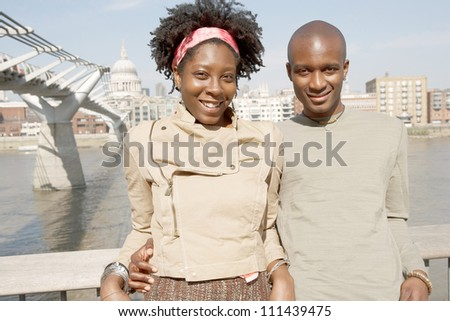 Portrait of a quirky black couple on vacations, visiting London city with the Millennium Bridge and St Paul's Cathedral behind them. - stock photo