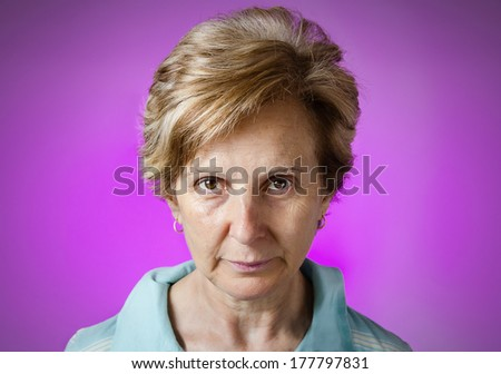 Portrait of a real serious middle aged woman over purple background - stock photo