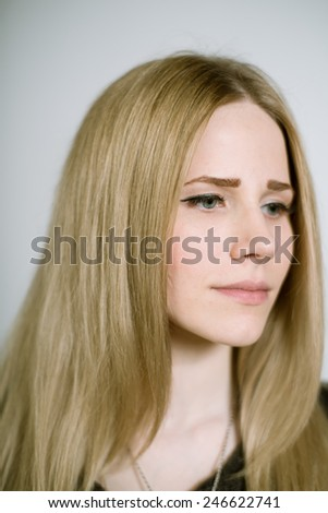 Portrait of a real young blonde woman on a light background in a black dress. Shallow depth of field. Focus on the eyelashes