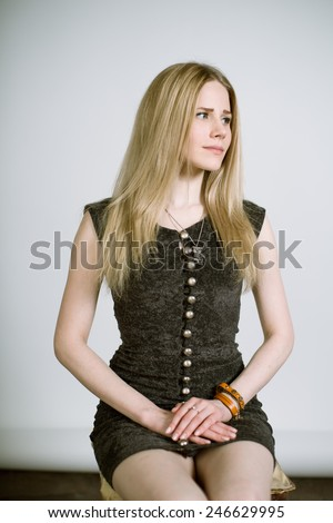 Portrait of a real young blonde woman on a light background in a black dress. Shallow depth of field. Focus on the eyelashes - stock photo