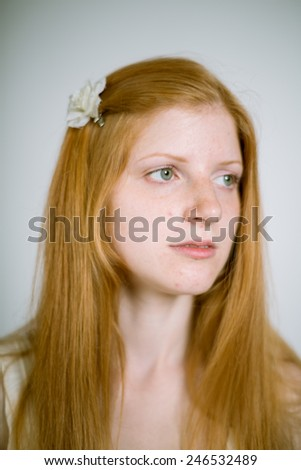 Portrait of a real young red-haired woman on a gray background with a flower in her hair. Shallow depth of field. Focus on the eyelashes