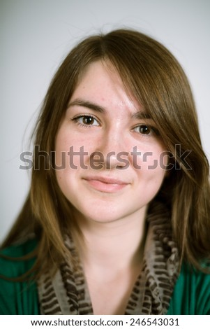 Portrait of a real young woman on a light background in a green cardigan. Shallow depth of field. Focus on the eyelashes - stock photo