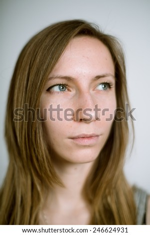 Portrait of a real young woman on a light background. Shallow depth of field. Focus on the eyelashes