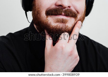 Portrait of a red-bearded, balding male brutal. White isolated background. A man in a black shirt . Headphones listening to music. keeps his chin, Smiling, holding chin showing middle finger. Closeup