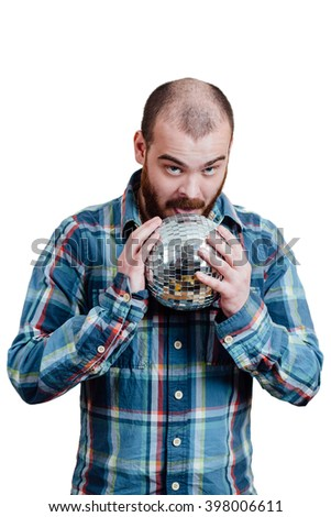 Portrait of a red-bearded, balding male brutal. White isolated background. A man in a blue plaid shirt. Holding disco ball in his hands and licking tongue