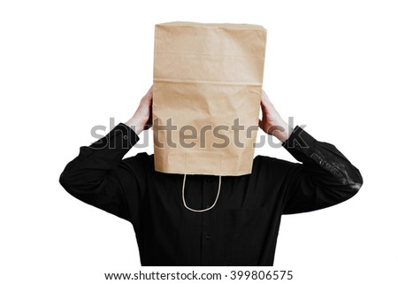 Portrait of a red-bearded, balding male brutal. White isolated background. Black shirt and pants. Paper bag over head. holding his head - stock photo
