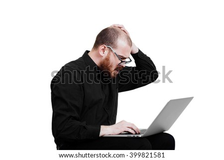 Portrait of a red-bearded, balding male brutal. White isolated. Man in a black shirt pants.  Sitting with laptop. Open mouth. Grandma's glasses. diopter Geek Looking  at computer.  Shocked businessman