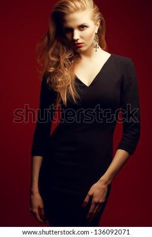 Portrait of a red-haired (ginger) fashionable model in a black classic cocktail dress posing over red background. Seductive glance. Vogue style. Studio shot - stock photo