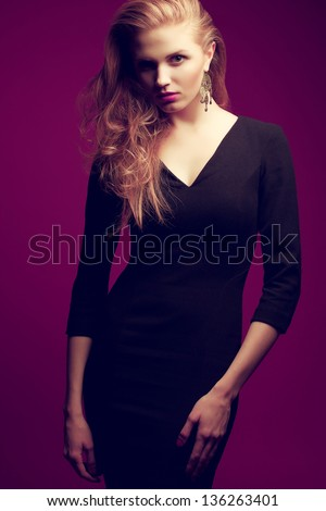 Portrait of a red-haired (ginger) fashionable model in a black classic cocktail dress posing over purple background. Seductive glance. Vogue style. Studio shot - stock photo