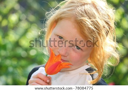 Portrait of a red haired girl holding a flower
