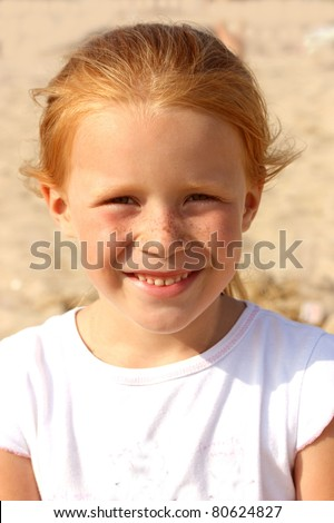 Portrait of a red-haired naughty girls at the age of 5 years - stock photo