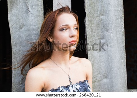 Portrait of a red-haired pretty young lady in floral dress looking at camera. Hair moving from wind - stock photo