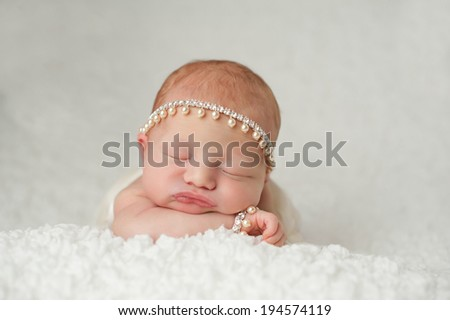 Portrait of a red headed, 2 week old, newborn baby girl. She is wearing a rhinestone and pearl headband and bracelet and is sleeping on a white, gauzy blanket. - stock photo