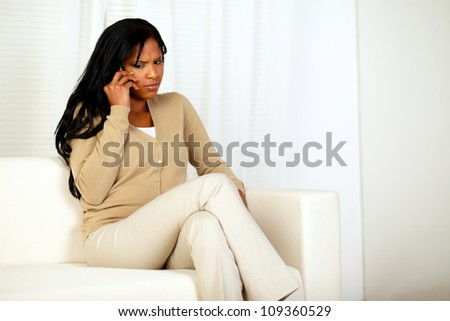 Portrait of a reflexive young woman conversing on cellphone while sitting on couch at home indoor - stock photo