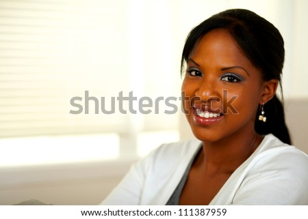 Portrait of a relaxed afro-American young female smiling at you at home. With copyspace