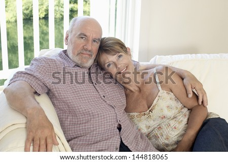 Portrait of a relaxed and loving middle aged couple sitting on couch - stock photo