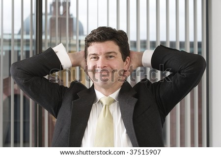 Portrait of a relaxed business man smiling with his hands behind his head. - stock photo