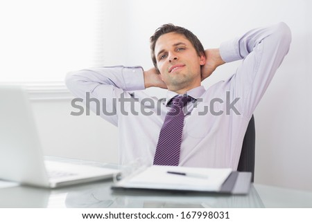 Portrait of a relaxed businessman sitting with hands behind head in a bright office