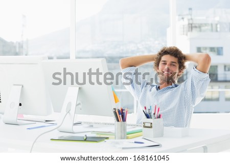 Portrait of a relaxed casual young business man with computer in a bright office - stock photo