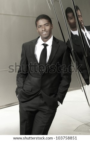 Portrait of a relaxed happy smiling businessman leaning on wall with hands in pockets - stock photo