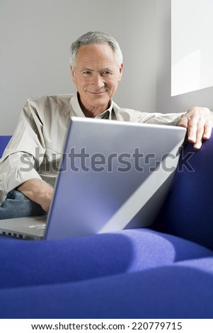 Portrait of a relaxed man sitting casually on a sofa looking as a laptop - stock photo