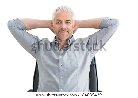 Portrait of a relaxed mature businessman with hands behind head over white background