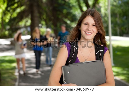 Portrait of a relaxed pretty college girl with binder - stock photo