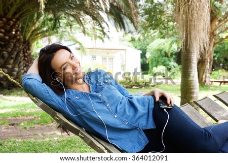 Portrait of a relaxed woman listening to music with earphones in the garden - stock photo