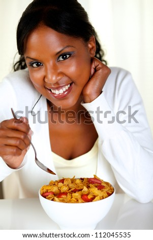Portrait of a relaxed woman looking at you and having breakfast at soft colors composition - stock photo