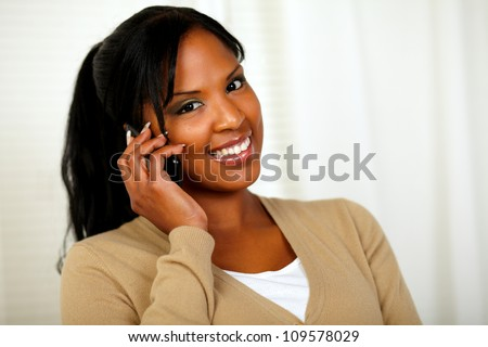 Portrait of a relaxed woman smiling at you with a cellphone - stock photo