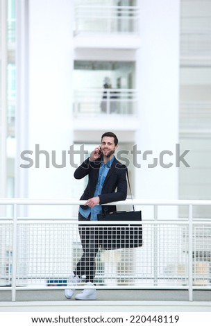 Portrait of a relaxed young businessman talking on mobile phone - stock photo