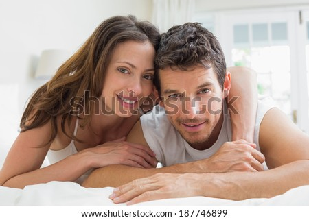Portrait of a relaxed young couple lying in bed at home - stock photo
