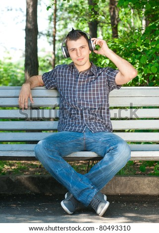 Portrait of a relaxed young man sitting on bench in park and listening to music on headphone