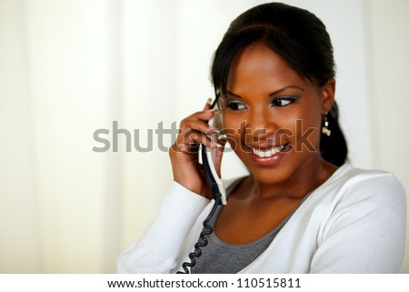 Portrait of a relaxed young woman conversing on phone at soft colors composition