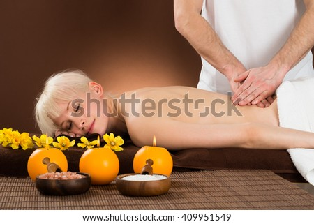 Portrait Of A Relaxed Young Woman Receiving Back Massage From A Massager In Beauty Spa - stock photo