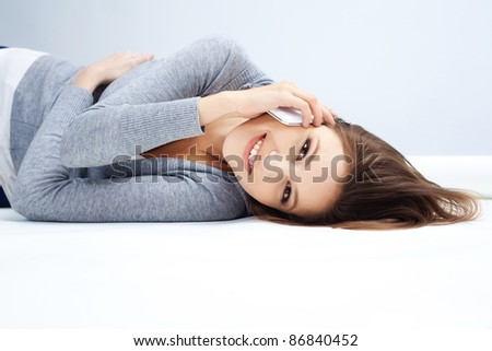 Portrait of a relaxed young woman talking on mobile phone - stock photo