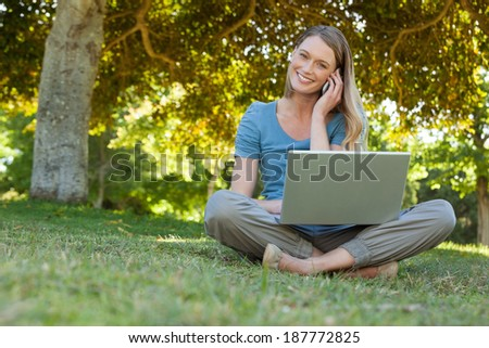 Portrait of a relaxed young woman using laptop and mobile phone at the park