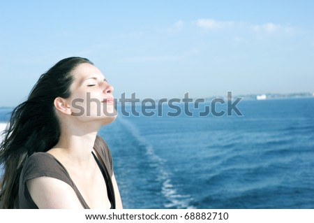 Portrait of a relaxing woman on the upper deck of a cruise ship - stock photo