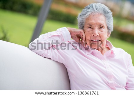 Portrait of a retired woman relaxing outdoors and looking happy - stock photo