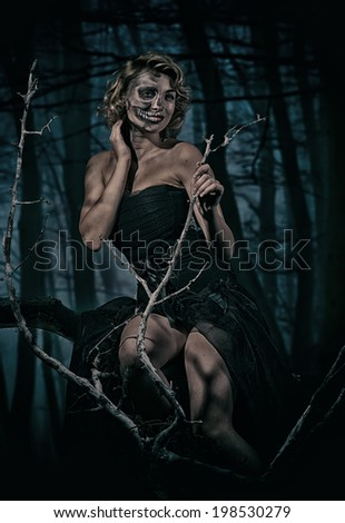 Portrait of a retro woman with skull make-up in the night forest - stock photo